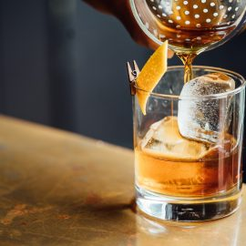 Rare Whisky being poured out of Boston shaker into glass with ice and orange peel