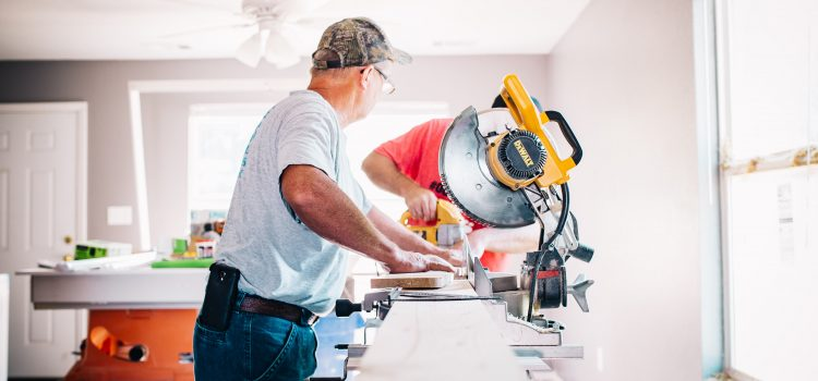 A male contractor at work on a large saw within a home