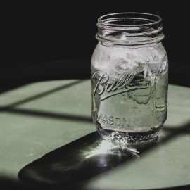Mason jar filled with ice water on a table